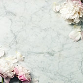 Flat-lay of Beautiful peony flowers over vintage marble background, top view, copy space