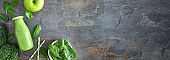 Banner with healthy green smoothie corner border, overhead view in milk bottle on a slate background with copy space