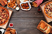 Variety of take out and fast foods, top view frame on a dark wood background