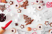 Christmas baking table scene with cookies and sweets. Top down view over white marble.