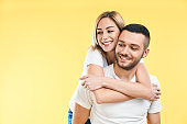 Happy smiling couple in love on yellow background with copy space