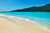 Turquoise clear sea and white sand beach on tropical island