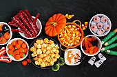 Halloween candy buffet table scene over a black stone background