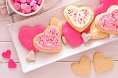 Heart shaped Valentines Day cookies with pink and white icing, overhead on a plate against white wood