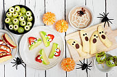 Healthy Halloween fruit snack table scene over a white wood background