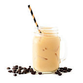 Cold iced latte in a mason jar with coffee beans isolated on white