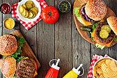 BBQ hamburger frame, above view over a dark wood background