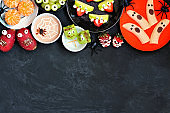Healthy Halloween fruit snacks. Overhead view top border over a black stone background.