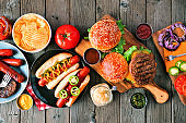 Summer BB table scene with hot dog and hamburger buffet, above view on a wood background