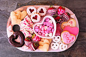 Valentines Day sweets and cookies, top view on a platter over slate