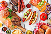 Summer BBQ food buffet with hot dogs and hamburgers, overhead table scene on a white wood background