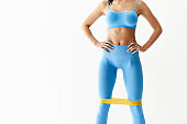 Sporty woman with resistance band loop workouts on white background with copy space