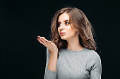 Alluring pretty woman blowing kiss Isolated on dark background