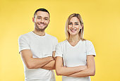 Young happy couple with arms crossed over yellow background
