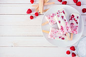 Plate of raspberry yogurt popsicles, above view corner border on a white wood background
