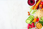 Selection of fresh vegetables and hummus, top view side border on a white marble background