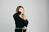 Young woman check her stomach fat with line tape, gesturing facepalm.
