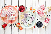 Variety of homemade berry yogurt popsicles, top view table scene over white wood