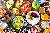 Healthy breakfast table scene with fruit, yogurts, smoothie bowl, oatmeal, nutritious toasts and egg skillet, above view over wood