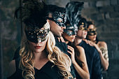 Group of people in masquerade carnival mask posing in studio