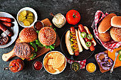 Summer BBQ food table with hot dog and hamburger buffet, flat lay over a dark background