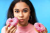 Hungry pretty girl eating donuts isolated over blue background
