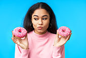 Thoughtful hungry woman choosing between donuts