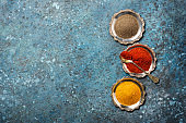 Bright ground seasonings in silver saucers with vintage spoon for spicy food
