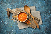 Raw red lentils in bowl with rustic wooden cutting board