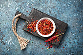 Red hot pepper flakes in white bowl and chilli pod on black wooden board