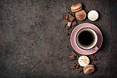 Top view of french dessert macaroons with chocolate and pink cup of coffee