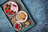 Bowls with oat flakes, raspberry, strawberry, blueberry, redcurrant, almond, hazelnut and fruit pink homemade yogurt