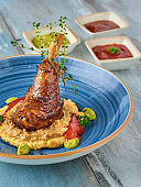 Braised lamb shank on the mashed potato on wooden table
