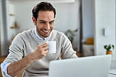 Happy male entrepreneur drinking coffee while using laptop at home.