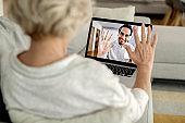 Close-up of woman having video call with her adult son over laptop.
