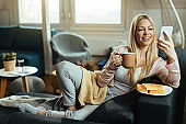 Happy woman drinking coffee and using smart phone while resting at home.