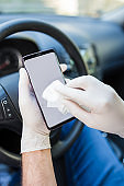 Man wearing protective medical rubber gloves disinfecting smartphone screen with wet wipe in car interior.
