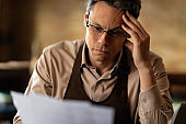 Distraught cafe owner reading reports while doing paperwork.