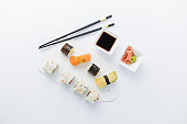 High angle view of sushi rolls and nigiri meal set with chopsticks, soy sauce, wasabi and gari on table.