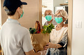 Happy mature woman and her husband receiving groceries at home during coronavirus epidemic.