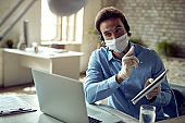 Businessman having online meeting over laptop at the office during COVID-19 pandemic.