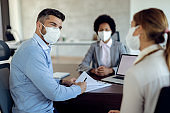 Man with protective face mask talking to his wife while signing contract with their insurance agent.
