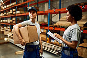 Two female workers communicating while working in distribution warehouse.