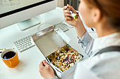 Close-up of businesswoman having a healthy meal while working in the office.