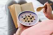 Close up of young pregnant woman sitting on bed and eating granola with cereals, blueberries and yogurt while reading book.