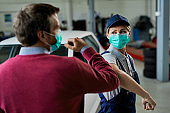 Car repairwoman and her customer elbow bumping while wearing protective face masks in a workshop.