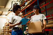 Below view of warehouse inspector and female worker talking about shipment schedule.
