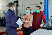 Couple with protective face mask receiving car keys from their mechanic in auto repair shop.