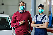 Female car mechanic and customer wearing protective face mask in auto repair shop.