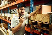 Happy worker talking over walkie-talkie while working in a warehouse.